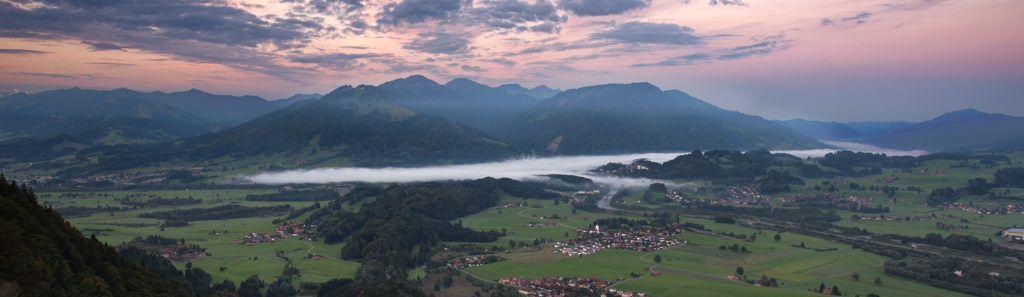 Landschaftsbild mit Abendrot und Nebel vom Berg ins Tal fotografiert